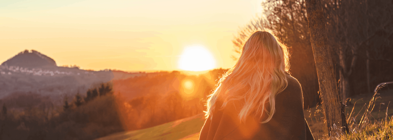 woman walking towards the sunrise