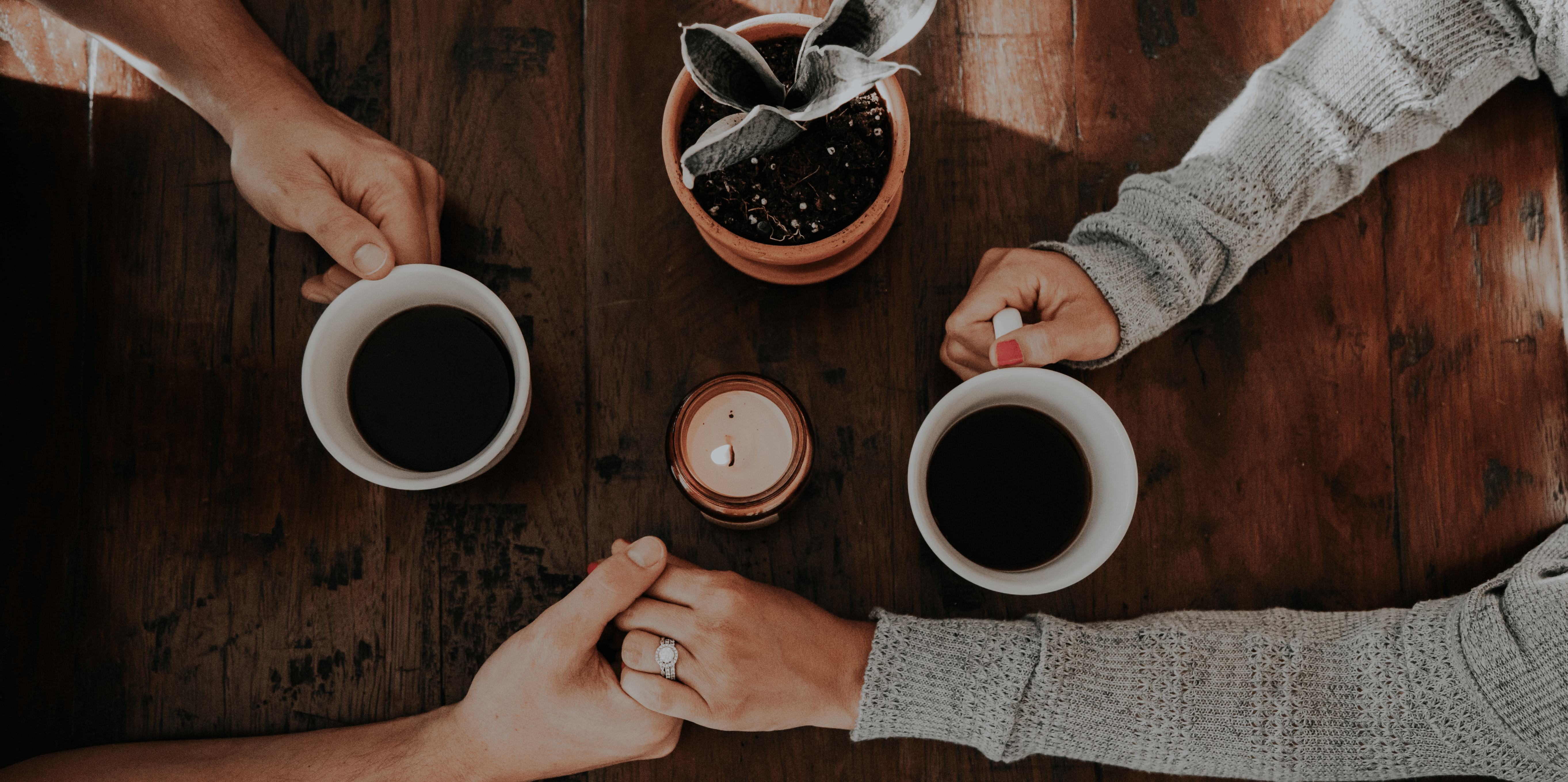 A married couple holding hands having a coffee.