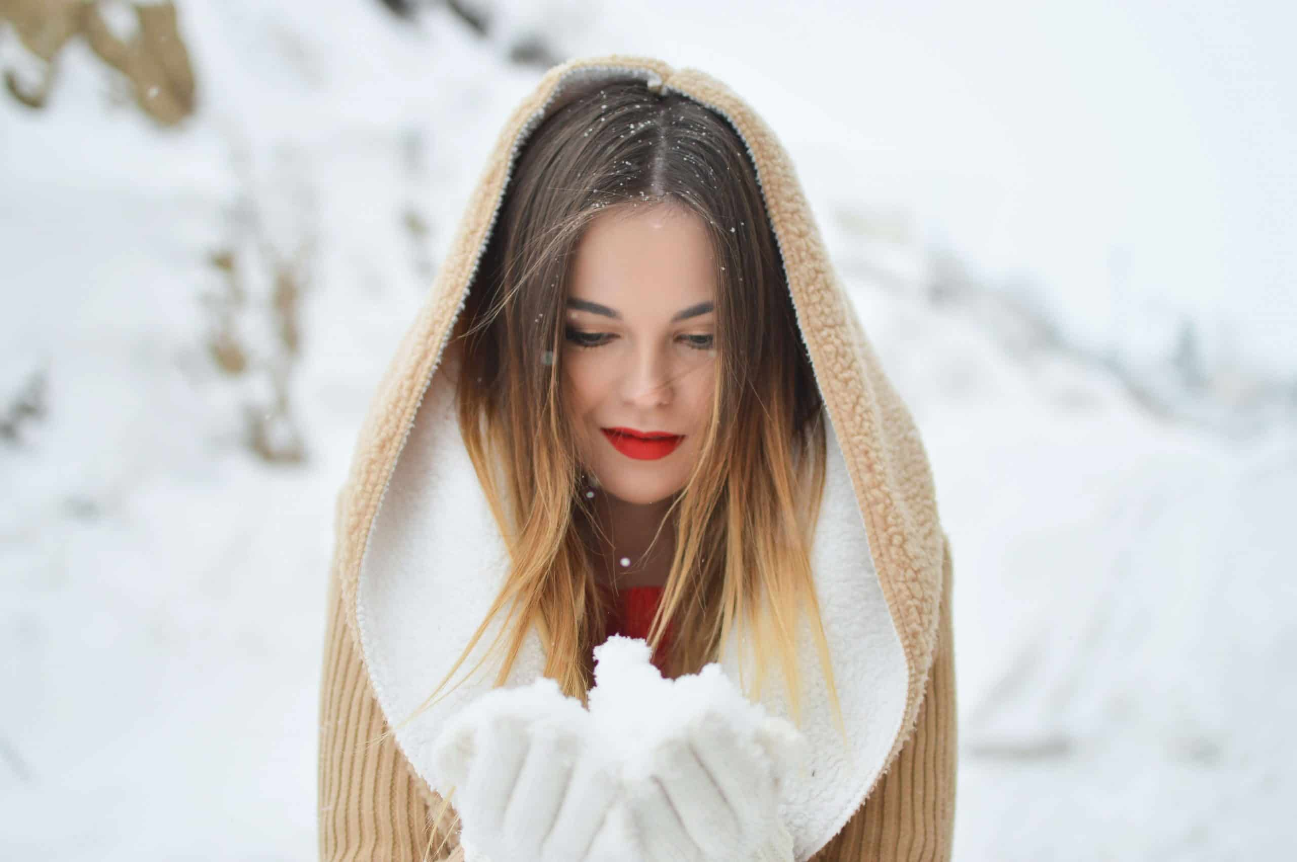 Woman holding a bit of snow in her gloved hands