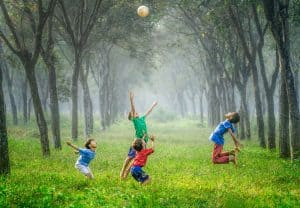 four kids having fun and playing ball outside