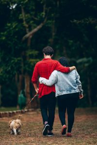 Date idea: couple taking a walk together with their dog