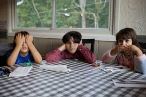three bored kids sitting at a table