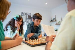 Kids and parents playing a board game together, making memories to prevent the summer slide.