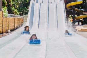 Kids going down a summer slide with water.