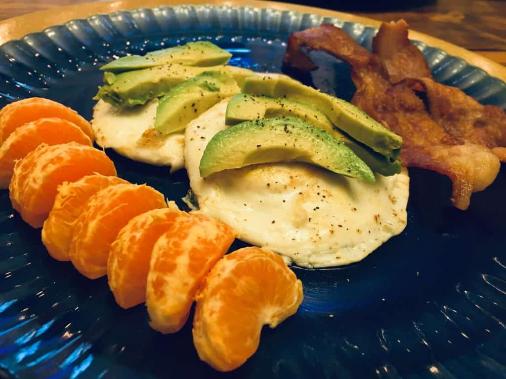 plate of eggs with bacon, avocado, and clementines for a frugal dinner