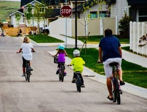 Family riding bikes together down a street, getting family exercise in summer