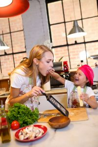 Mother and child cooking together, mastering new skills