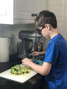boy chopping broccoli