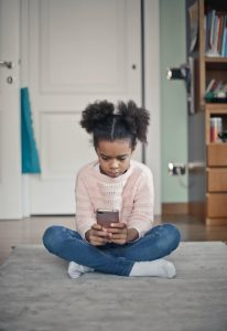 Girl sitting on bedroom floor looking at her cell phone