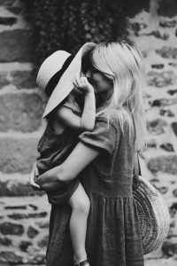 mom holding her daughter and giving her a kiss