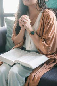 woman praying with an open bible