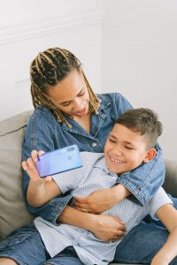 Mom snuggling son on the couch as he holds a cell phone