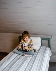 boy sitting on his bed as he looks at his cell phone