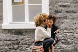 mom whispering a secret in her daughter's ear